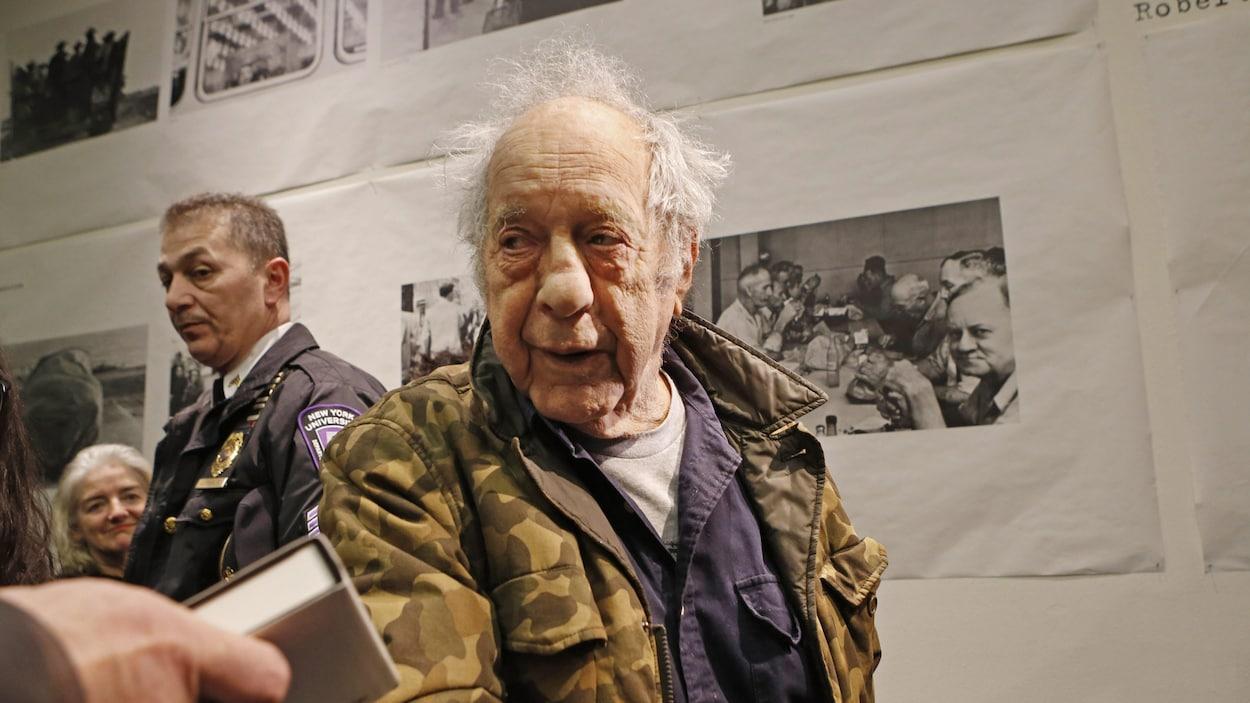 L'homme est devant une série de photos tirées de son livre.