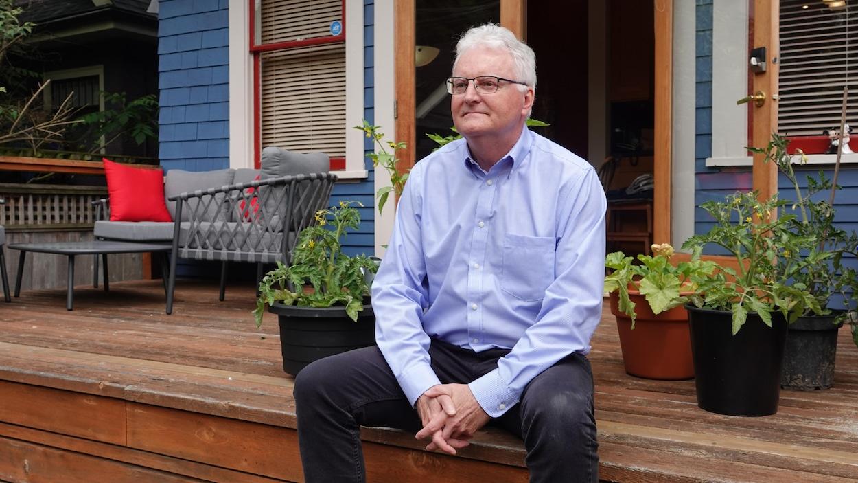 Robert Grant est assis sur son patio derrière sa maison, devant des plants de légumes.