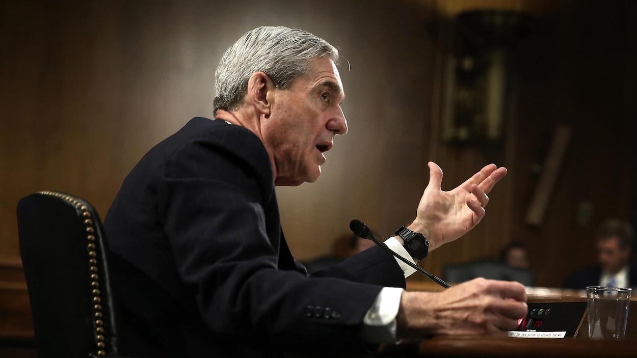 Assis derrière un bureau, un homme parle dans un micro.