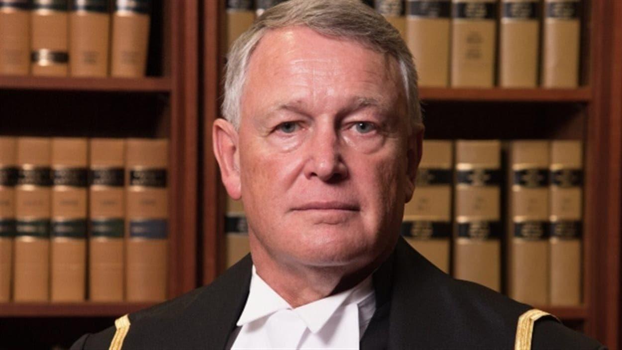 Le juge Robin Camp en habit de magistrat, devant une bibliothèque