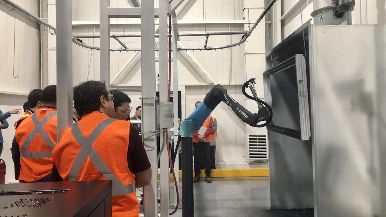 Des employés et des invités regardent le robot métallique s'exécuter. Il peint un cadre de fenêtre.