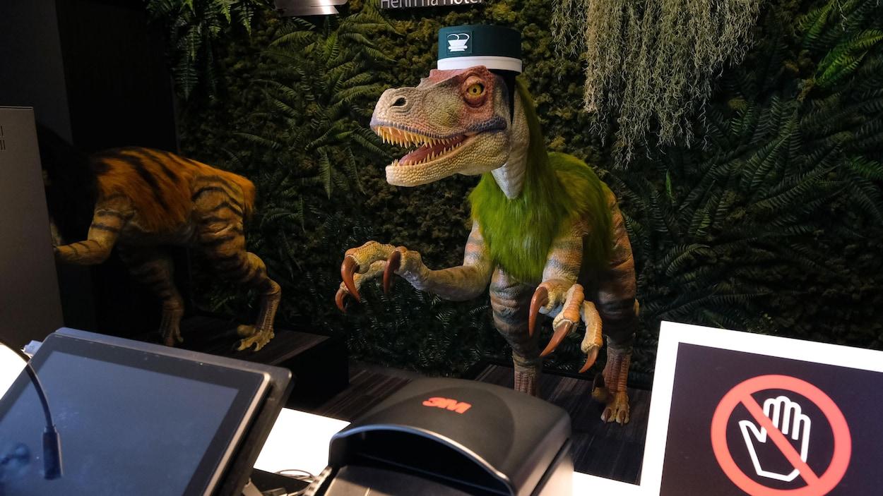 Un robot à l'apparence de vélociraptor se tient derrière un comptoir de réception à l'hôtel Henn-na.