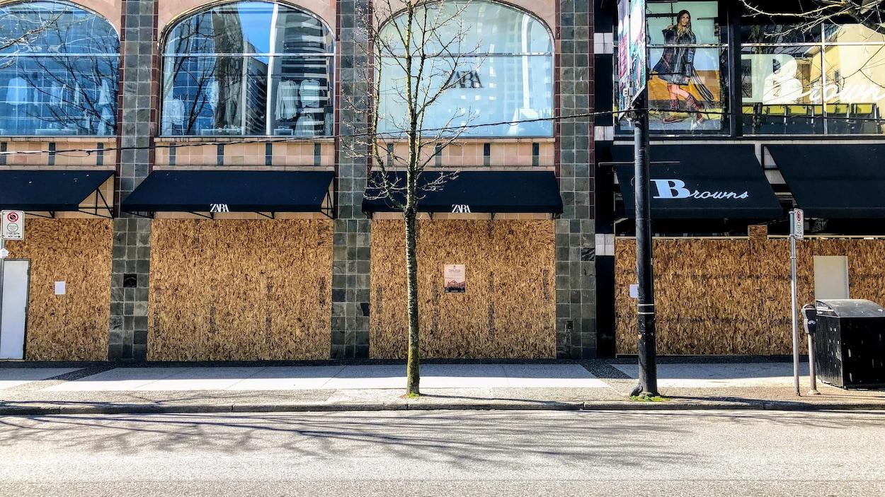 Les magasins Zara et Browns de la rue Robson sont fermés avec des planches de bois devant leur vitrine.