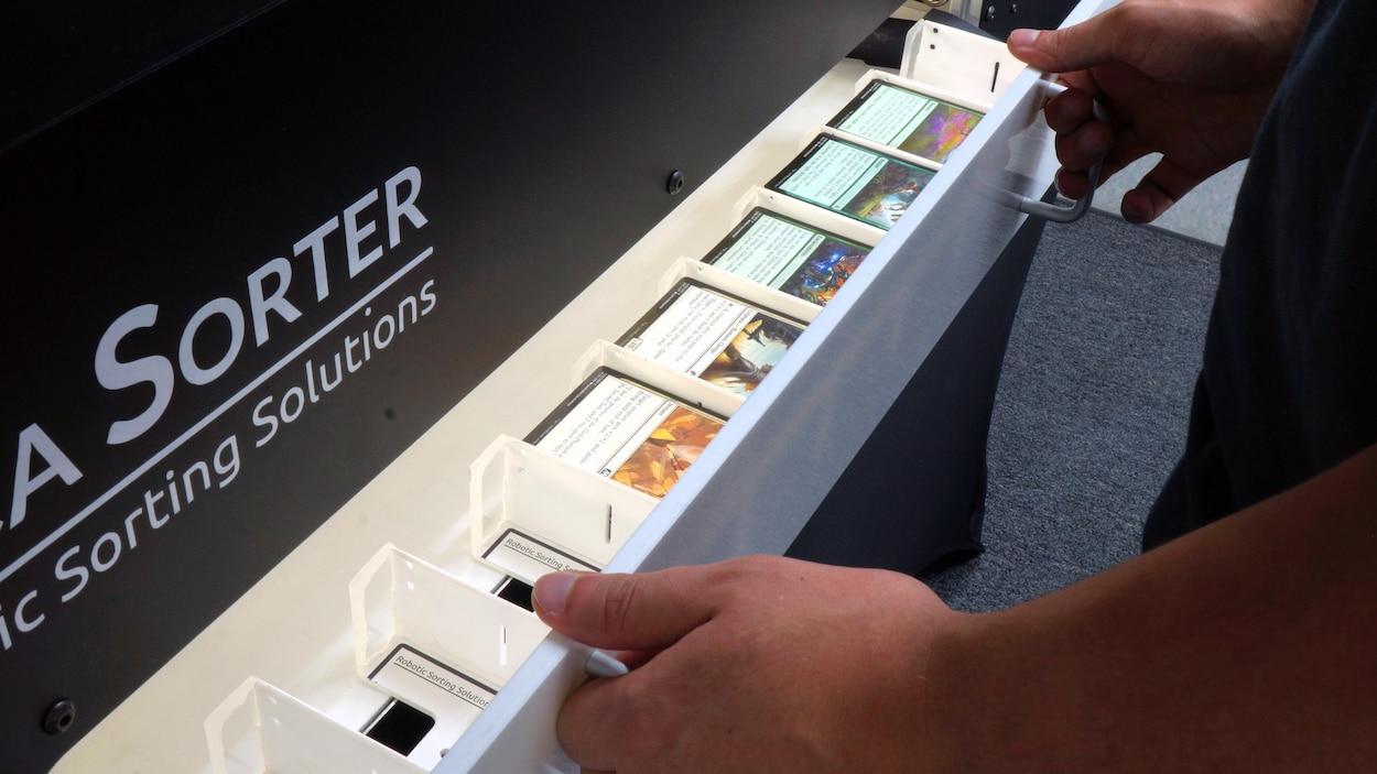 Un homme tire sur le tiroir servant à placer les cartes à trier dans la machine.