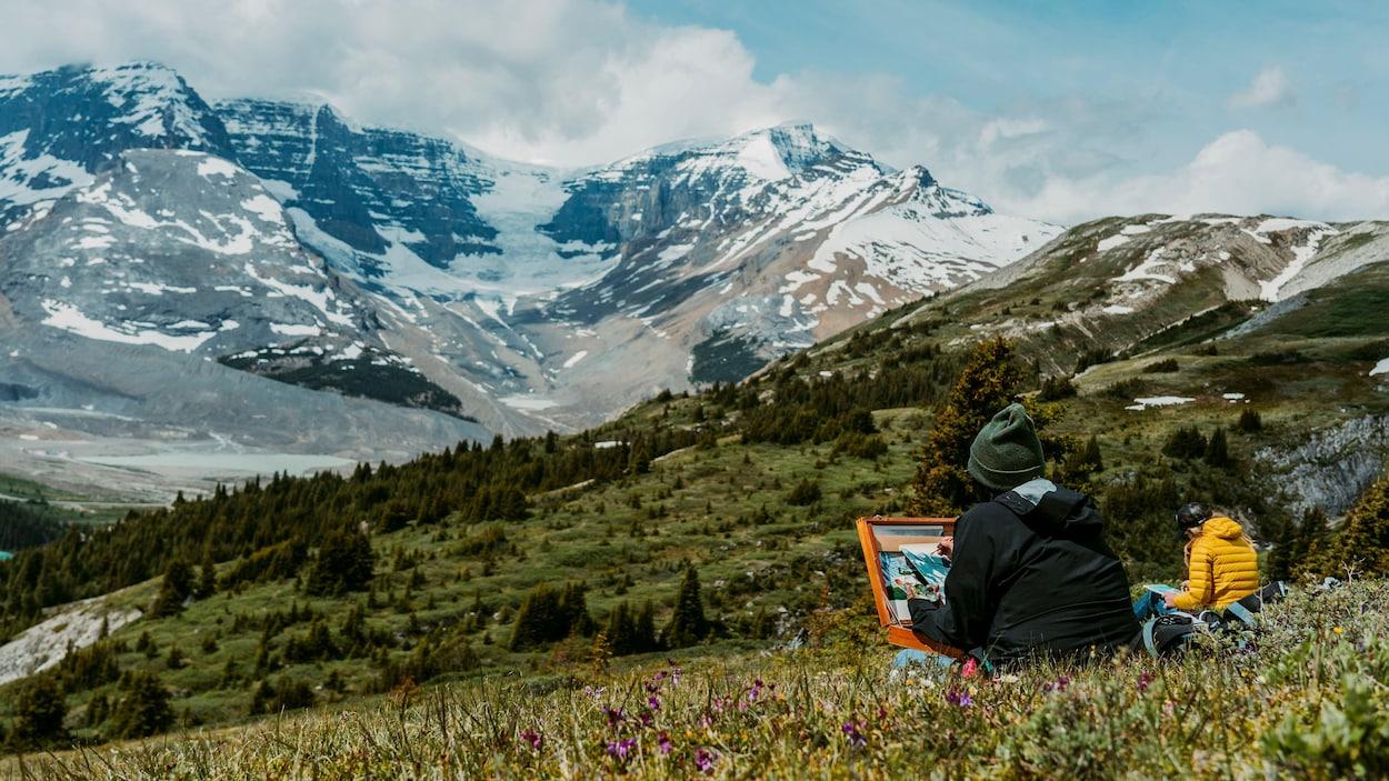 Deux artistes sont en train de peindre dans les montagnes.