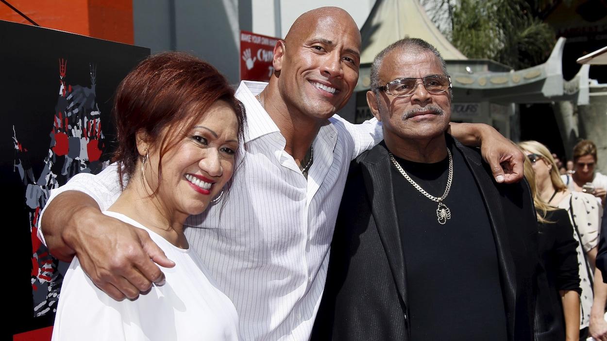 Dwayne Johnson a les bras autour des épaules de ses parents.