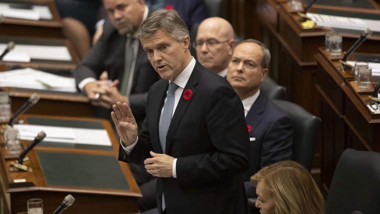 Le ministre est debout en chambre et parle devant ses collègues.