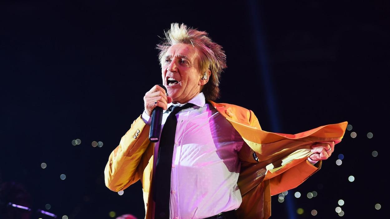 Un homme vêtu d'un veston orange chante, un micro à la main, sur scène.