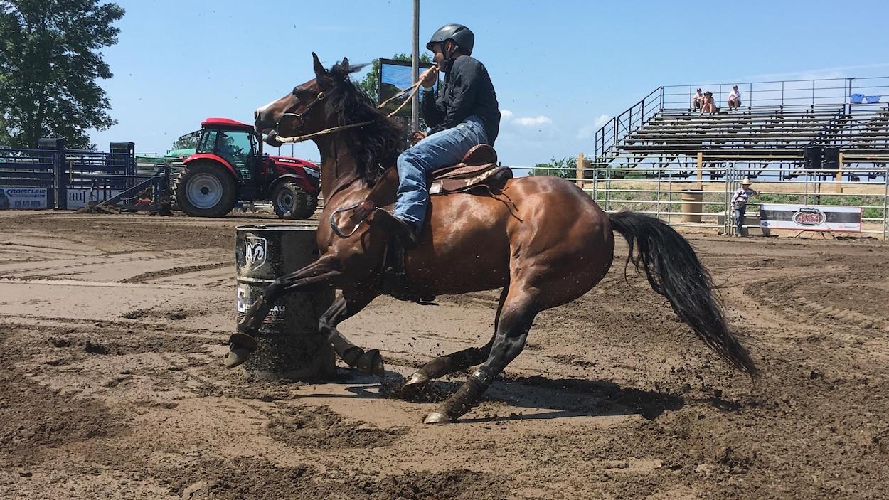 Un cavalier sur son cheval contourne un baril dans un manège.