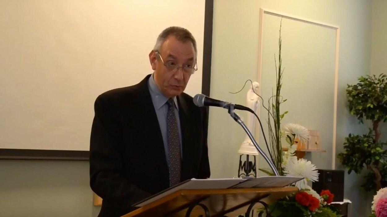 Un homme à lunettes en costume sombre parle dans un microphone.