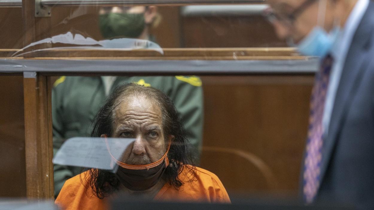 Assis dans un cubicule d'un palais de justice où les détenus assistent à une audience, l'acteur Ron Jeremy écoute un avocat parler.