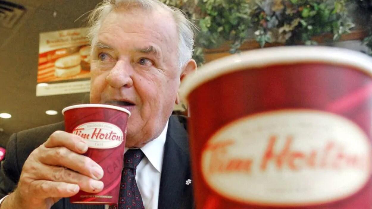 Ron Joyce a un café Tim Hortons à la main.