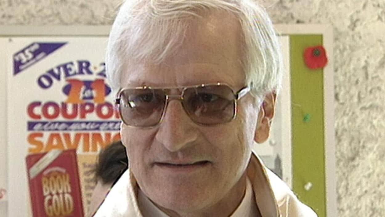 Un homme aux cheveux blancs portant des lunettes regarde vers la droite