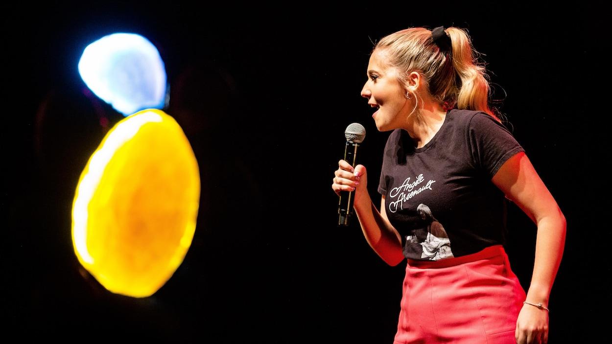 La jeune femme avec un chandail noir et une jupe rose tient un micro dans sa main. Elle est sur scène pour son spectacle d'humour.