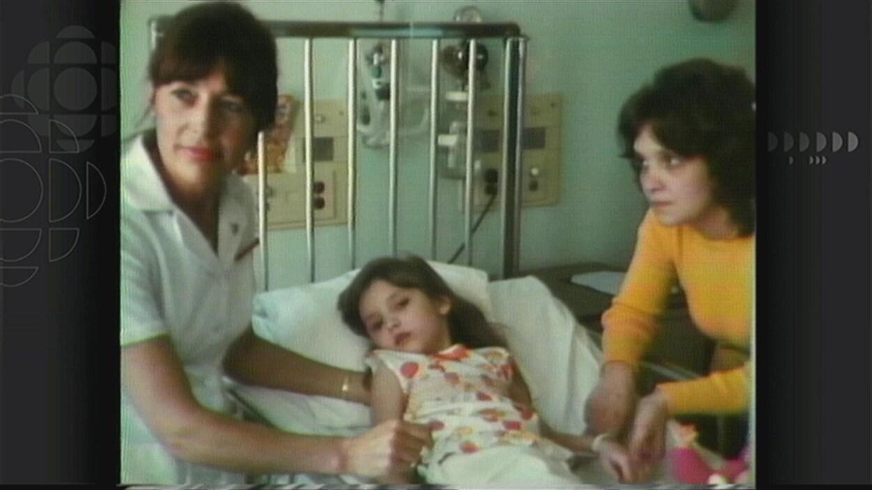La jeune Caroline accompagnée de sa mère (à droite) et d'une infirmière (à gauche) sur un lit d'hôpital.