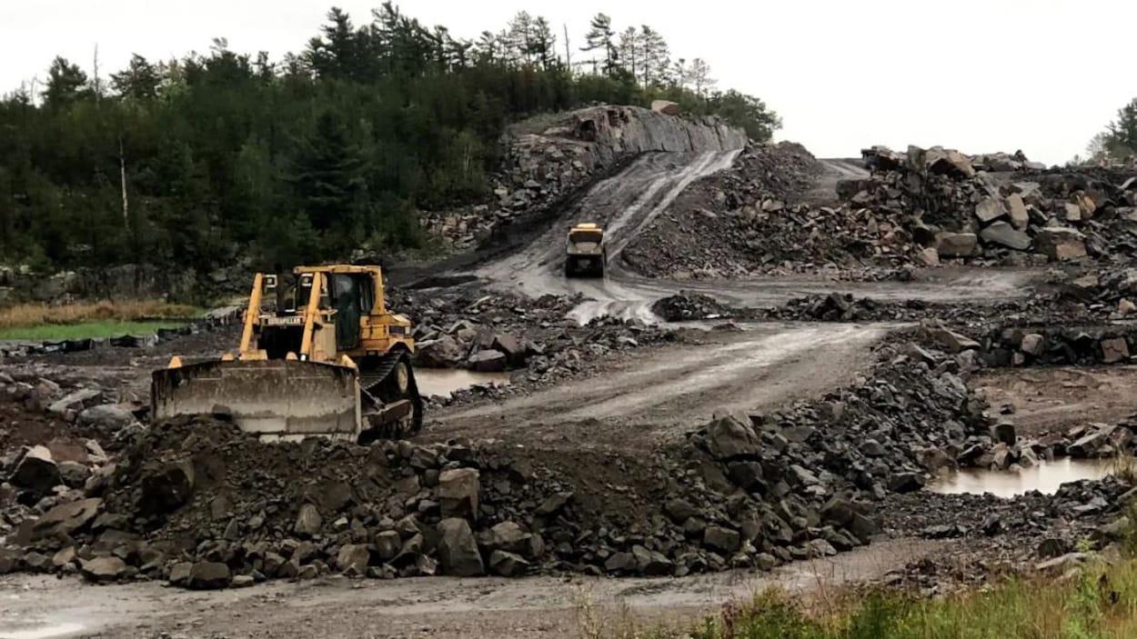 Des tracteurs effectuent des travaux de réparation d'une route.