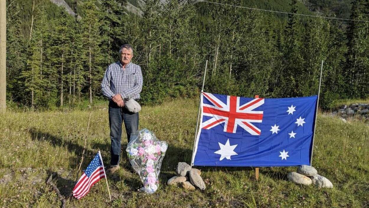Un homme se tient chapeau à la main aux côtés d'une croix fleurie avec d'un côté un drapeau australien et de l'autre, un drapeau américain.