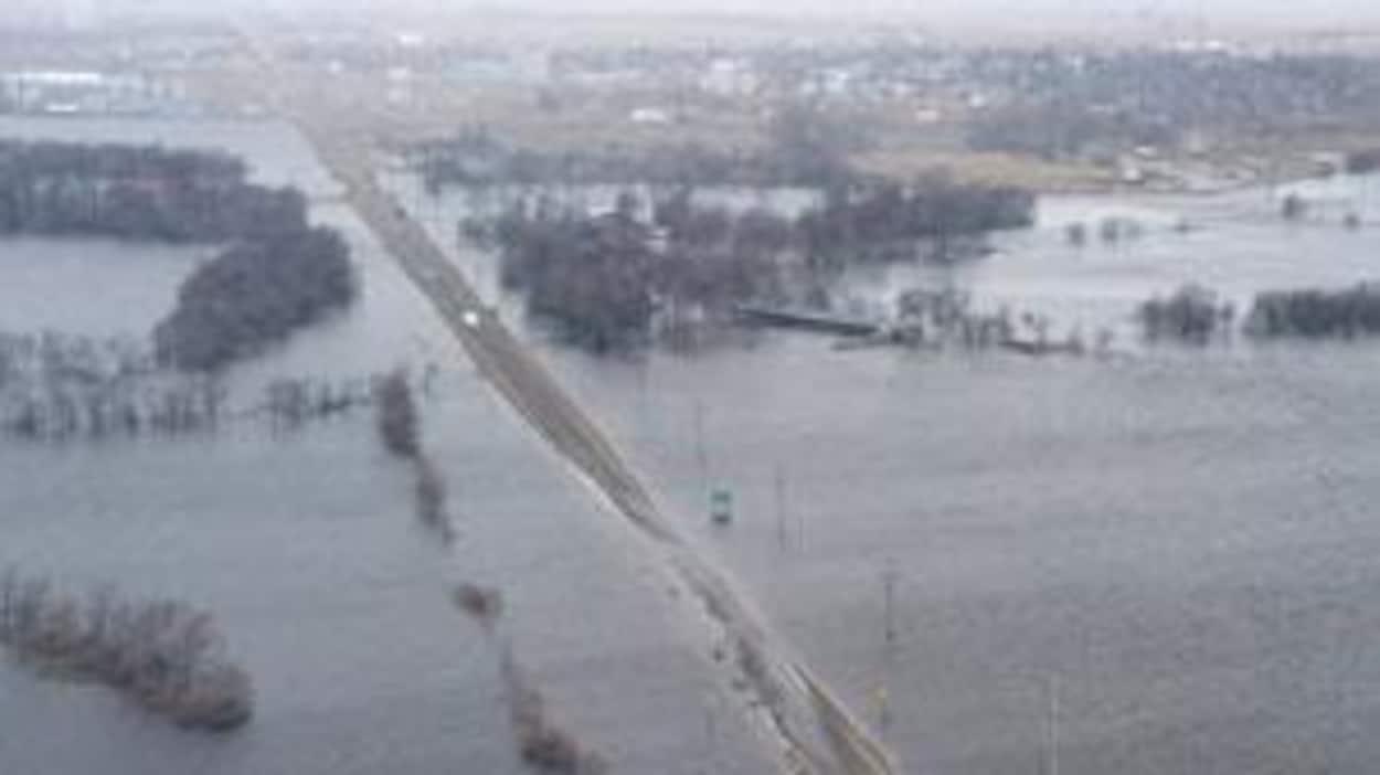 Une route et des champs inondés.