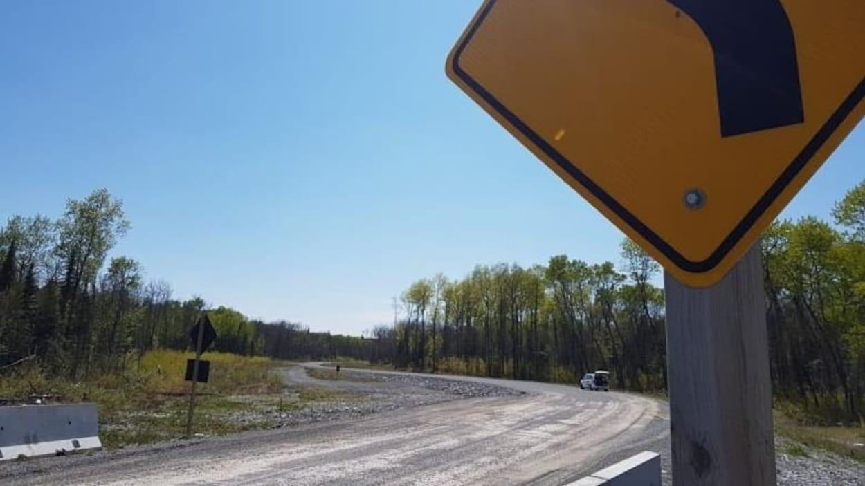 Un panneau est positionné devant une route qui traverse des terrains forestiers.
