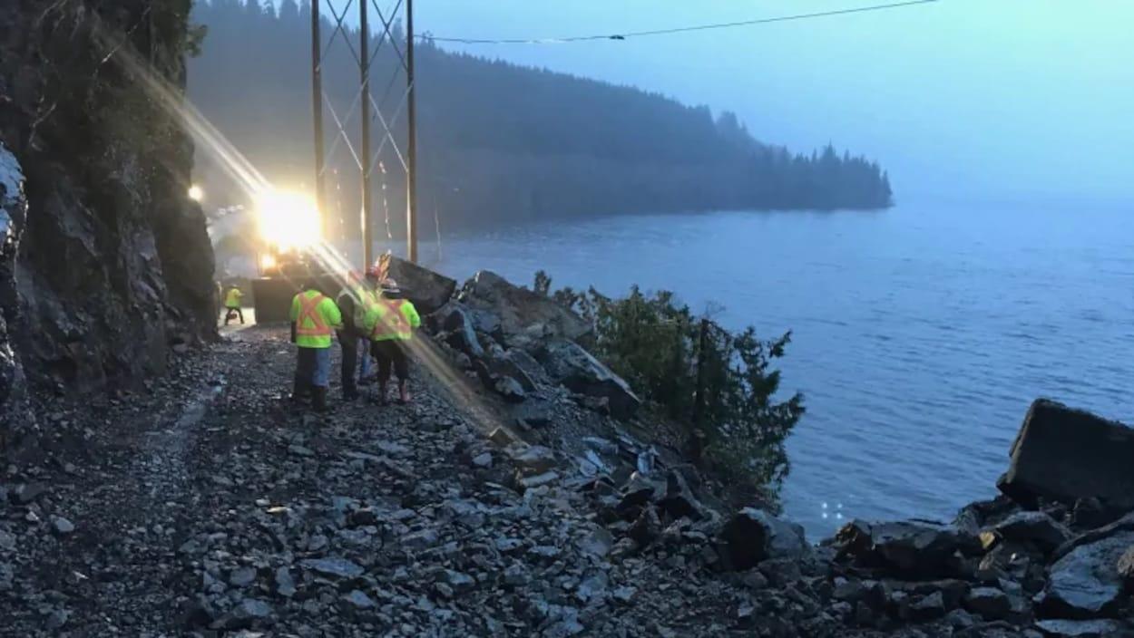 Des ouvriers sur une route remplie de gros cailloux le long d'un lac.