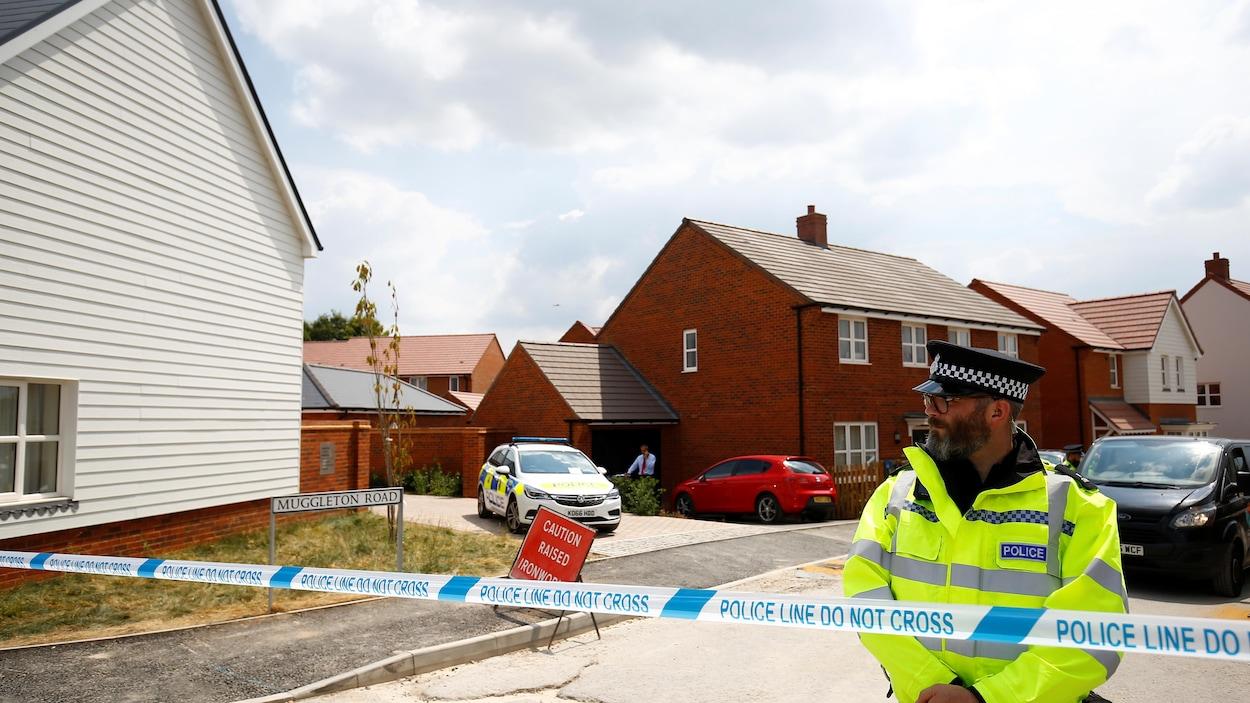 Un policier devant une série de maisons.