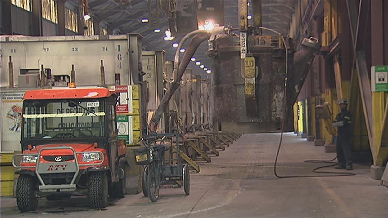 Un travailleur déplace de l'équipement à l'intérieur de l'usine Grande-Baie de Rio Tinto.