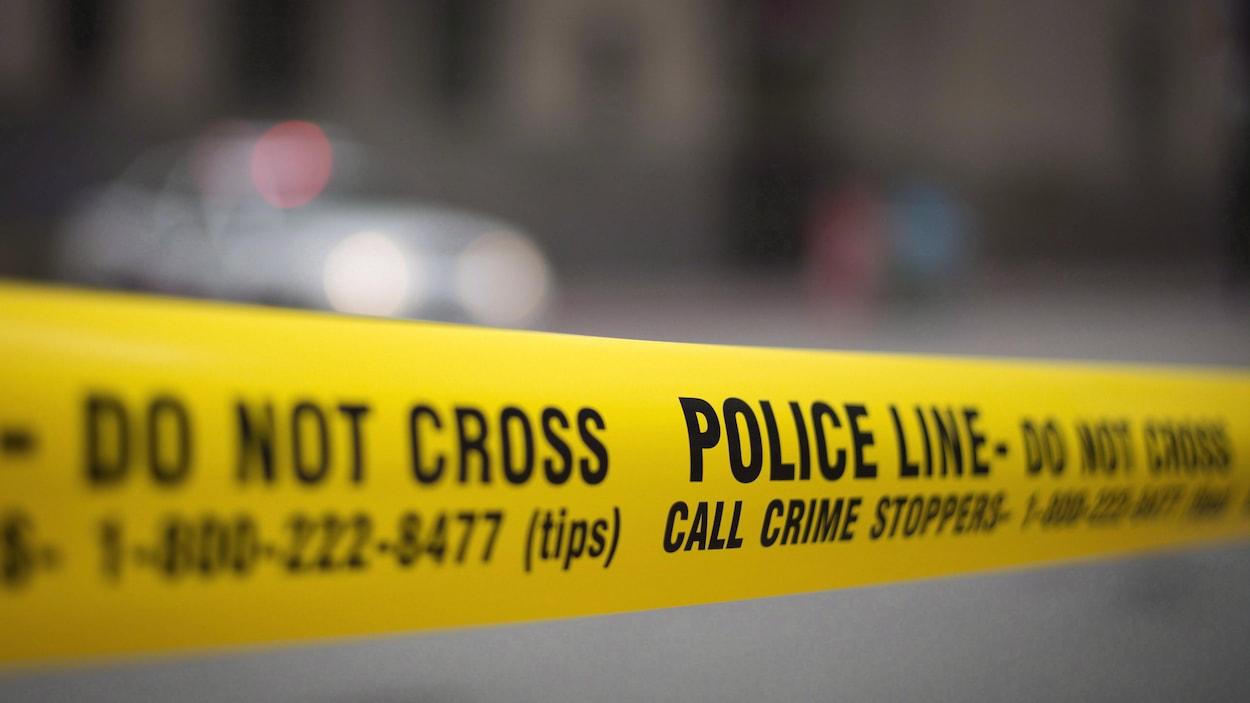 Un ruban jaune de scène de crime et une autopatrouille au loin.