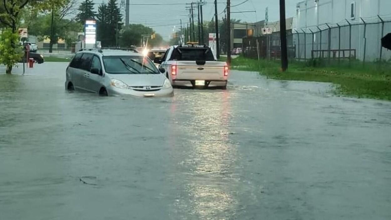 Des véhicules roulent dans une rue avec de l'eau à hauteur des portières.