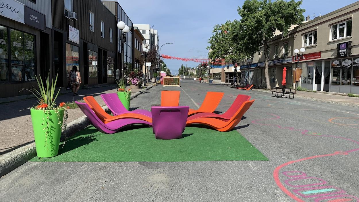 Des bancs colorés installés dans la rue, avec des dessins sur l'asphalte et des banderoles au dessus du trottoir.