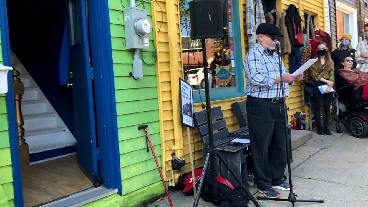 Un homme parle au micro. Derrière lui, deux maisons très colorées de la rue Queen. Des citoyens sont aussi présents.