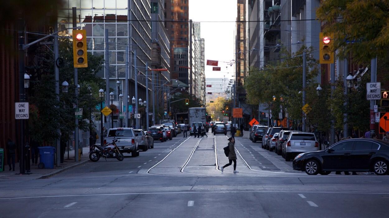 Un piéton traverse une rue du centre-ville de Toronto.