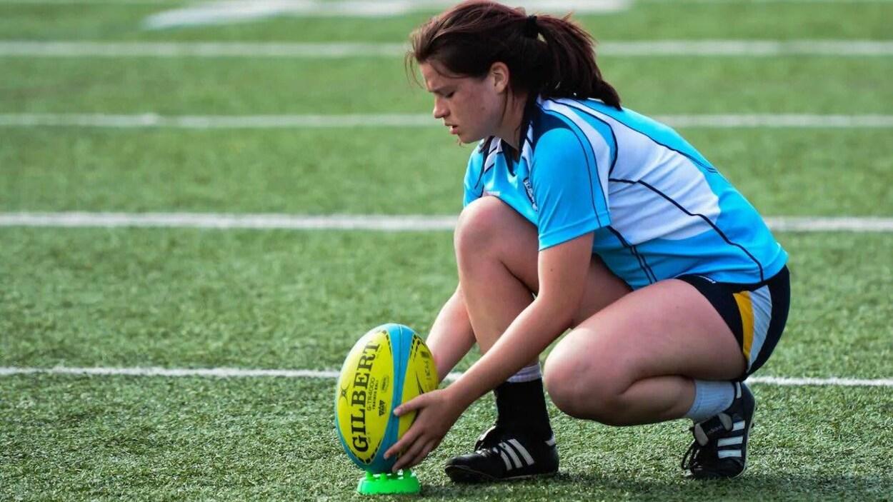 Joueuse de rugby agenouillée devant le ballon.