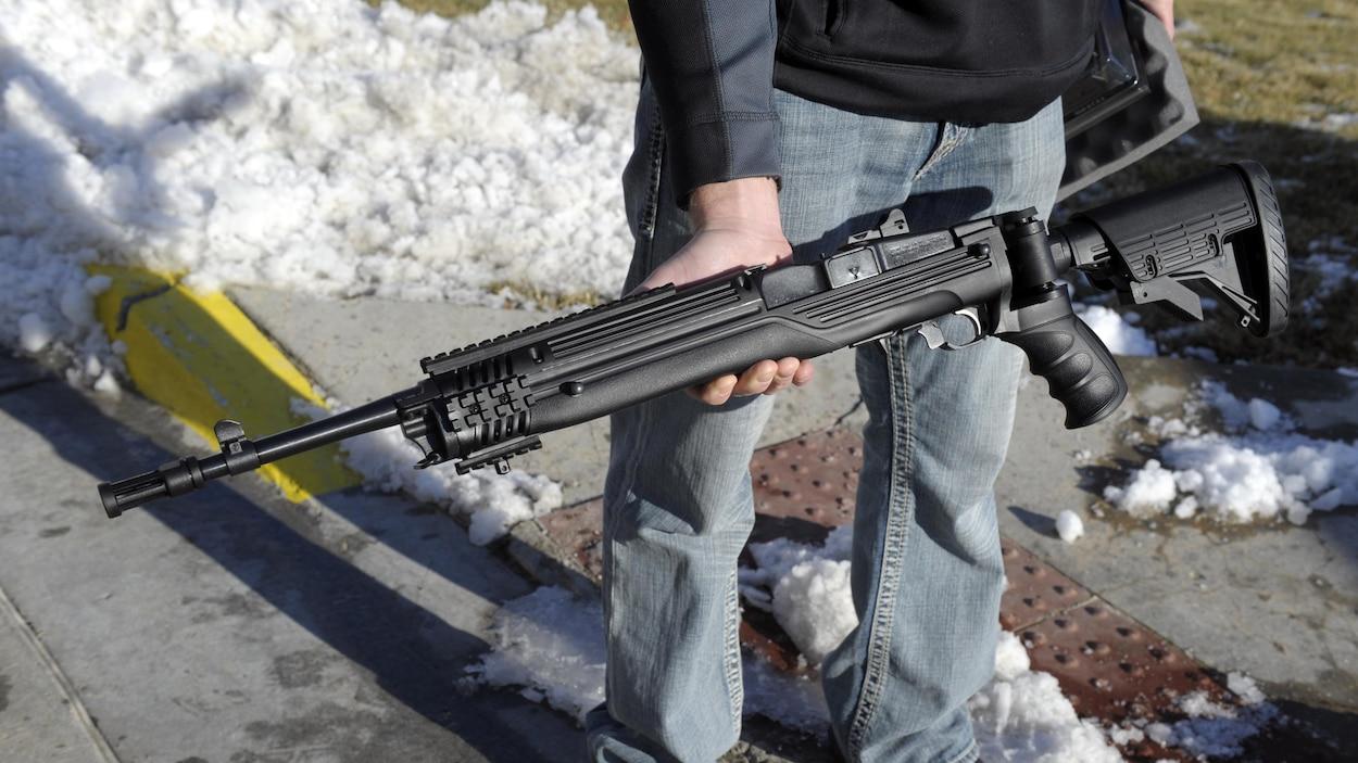 Un homme tient un fusil dans ses mains.