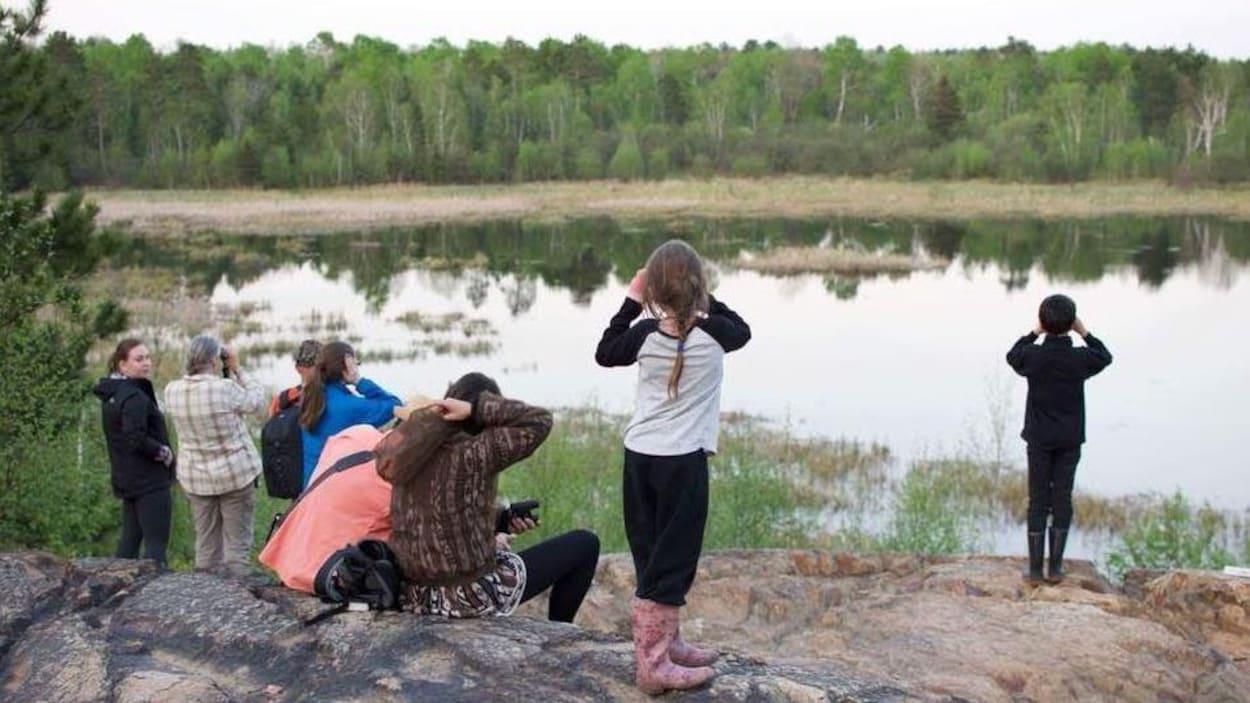 Une demi-douzaines de personnes observent un marais avec des jumelles.