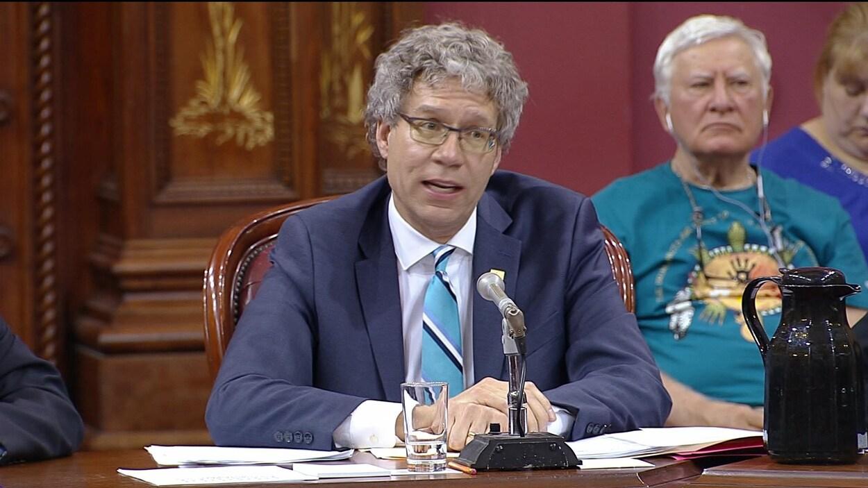 Un homme témoigne en commission parlementaire.