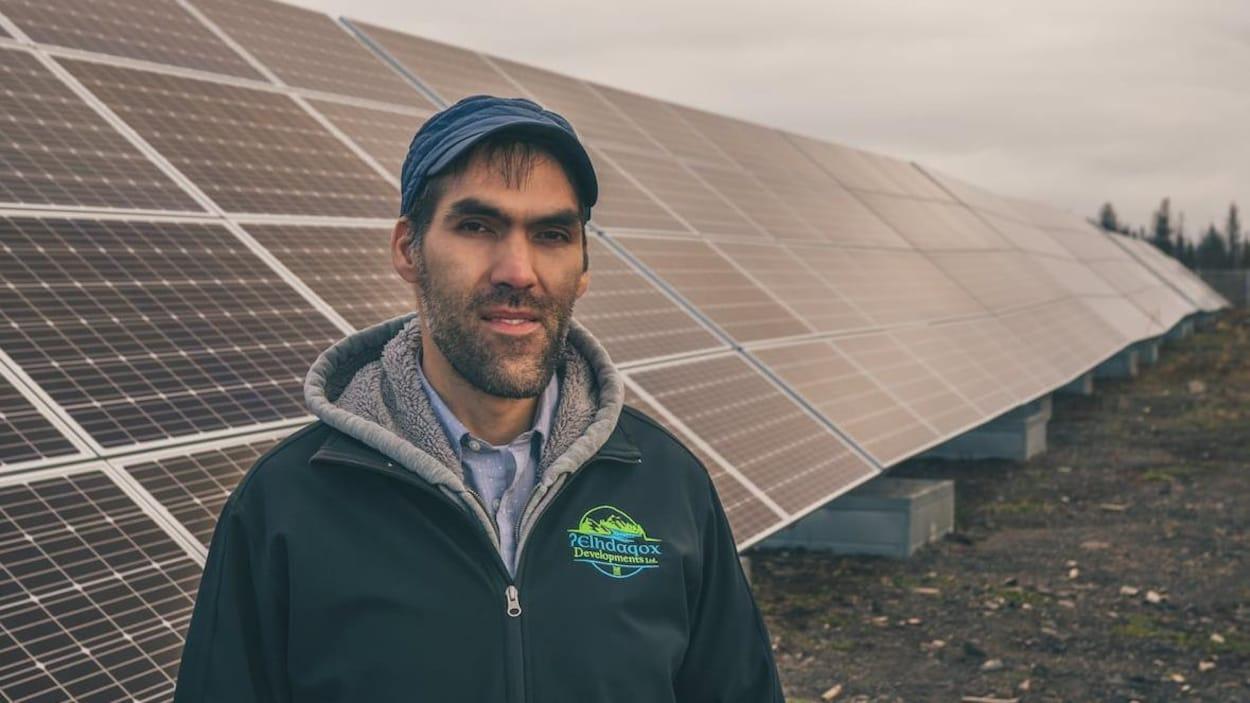 Plan moyen de Russell Myers Ross debout devant une rangée de panneaux solaires.