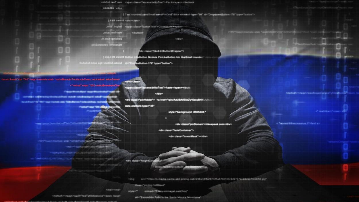 Une photo montrant une personne au visage obscurci par le capuchon de son chandail noir. Derrière lui flotte un drapeau de la Russie.