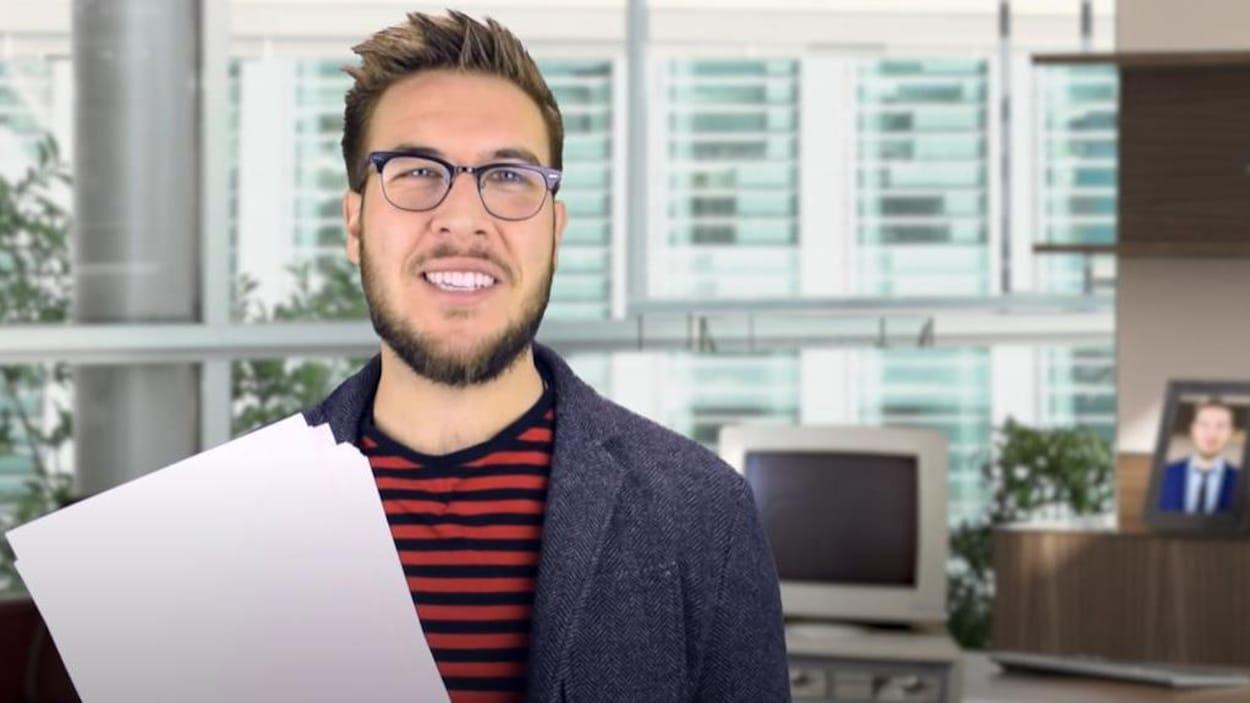 Ryan George jouant le rôle d'un scénariste dans une des vidéos. Il porte des lunettes et a des feuilles de papier dans les mains.