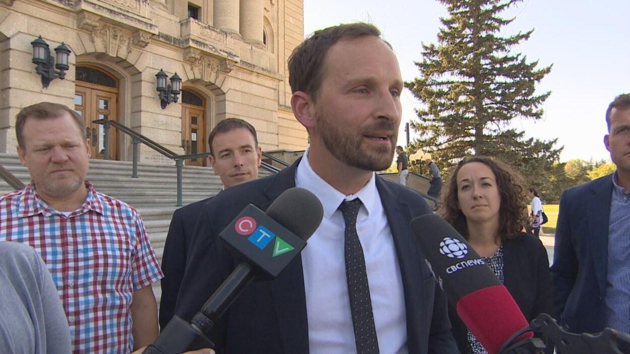 Un homme grand et fin (Ryan Meili), avec quatres personnes et le bâtiment législatif derrière lui, parle pendant un point de presse.