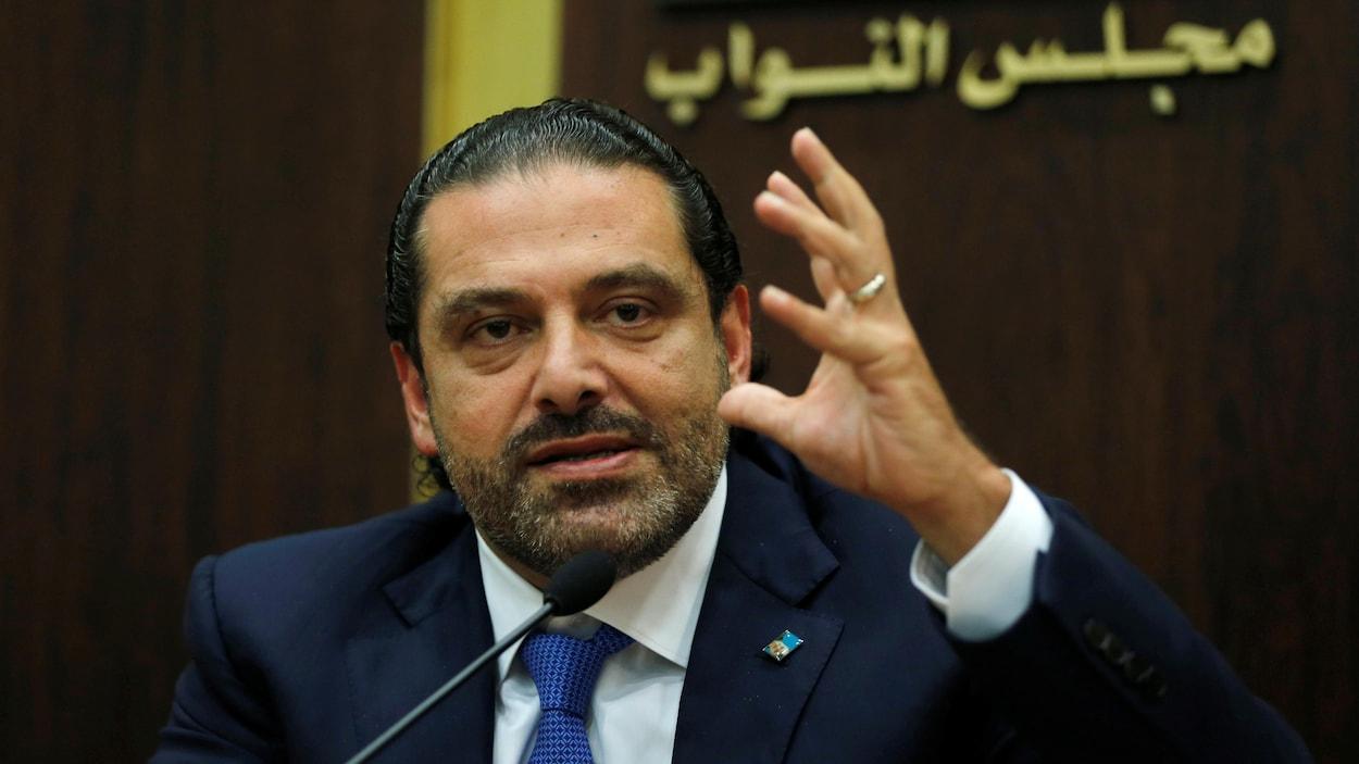 Saad Hariri, qui porte un complet bleu marine, lève la main gauche.