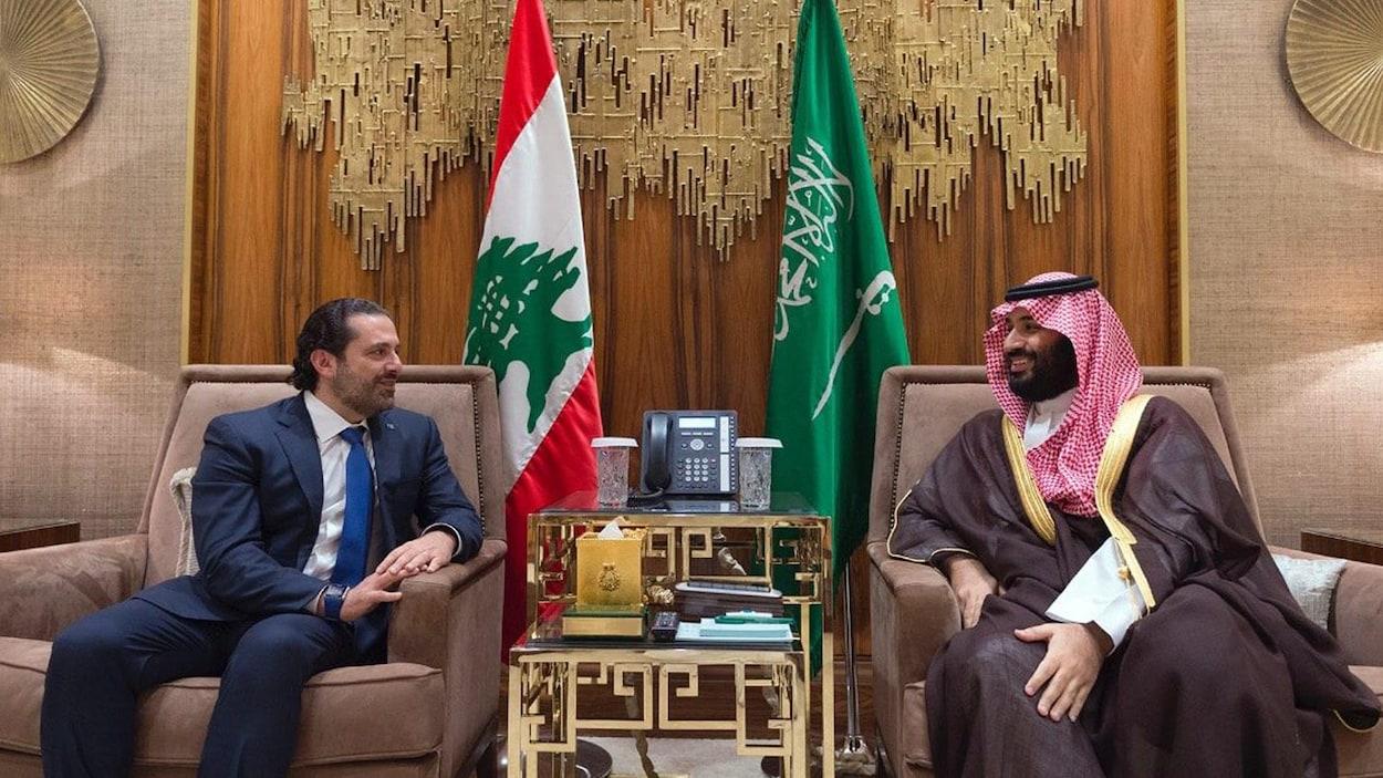 Les deux hommes sont assis devant des drapeaux de leurs pays respectifs.