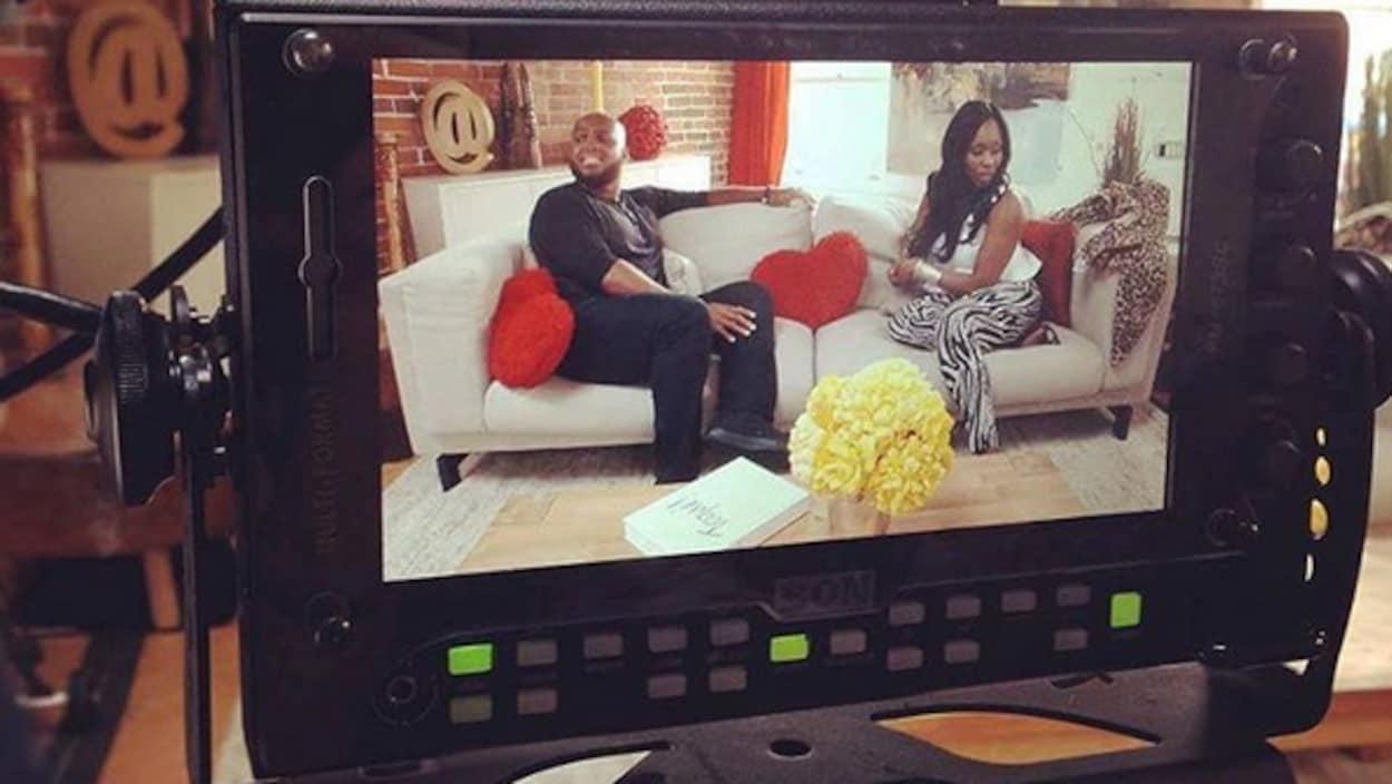 Un écran de caméra dans lequel on voit un tournage d'une émission de télé mettant en vedette deux personnes à la peau noire.