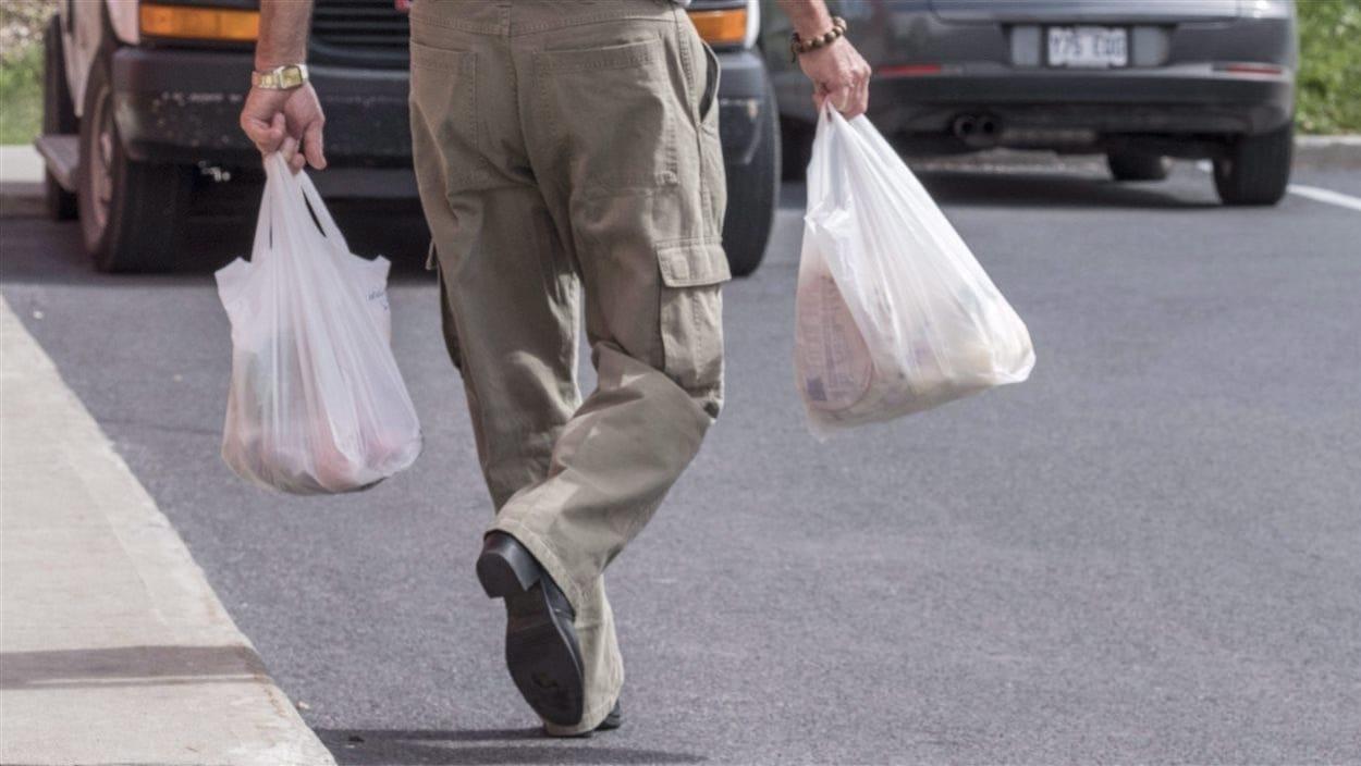 Un homme transporte ses emplettes dans des sacs en plastique.
