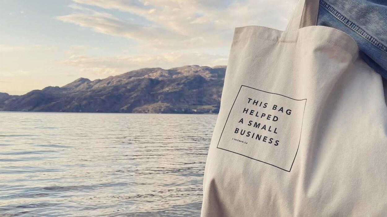 Une personne porte un sac sur lequel on peut lire en anglais : Ce sac a aidé une petite entreprise.
