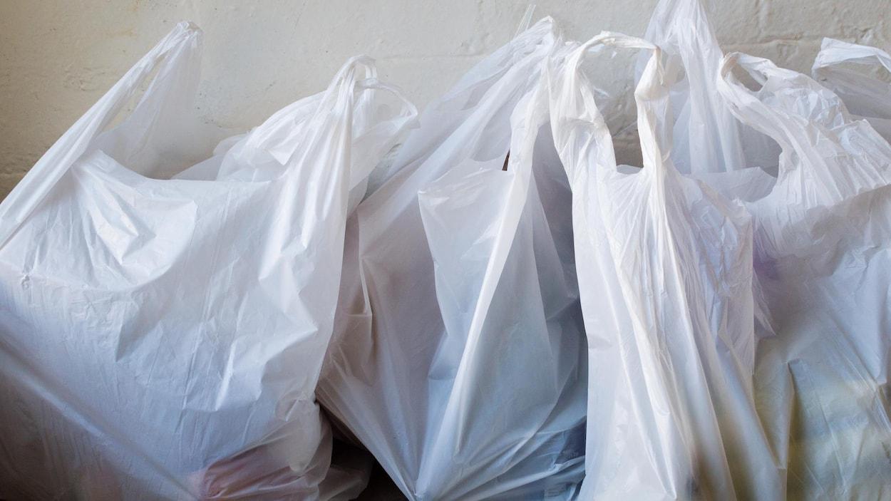 Trois sacs de plastique pleins de victuailles sur le plancher.