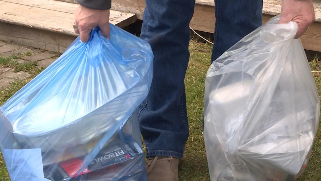Un homme tient un sac de recyclage et un sac à ordures.