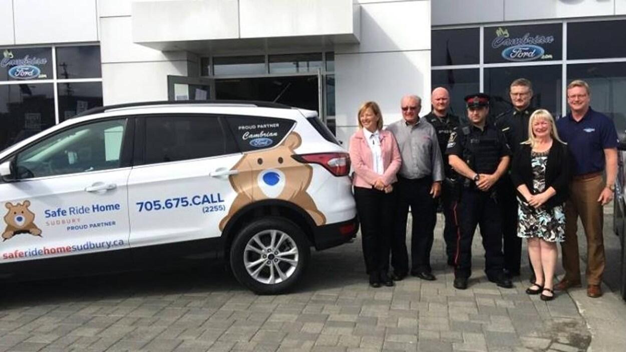 Un groupe de personnes à côté d'une voiture portant le logo de Safe Ride Home