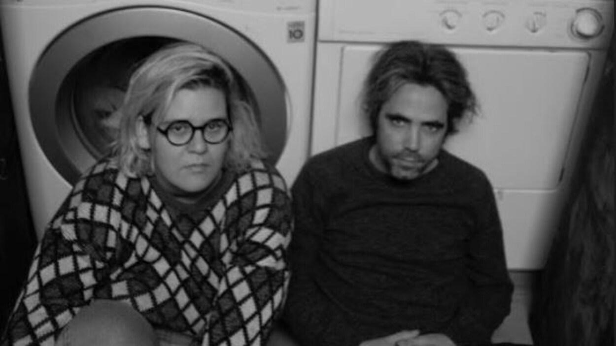 La femme et l'homme sont devant une laveuse et une sécheuse.