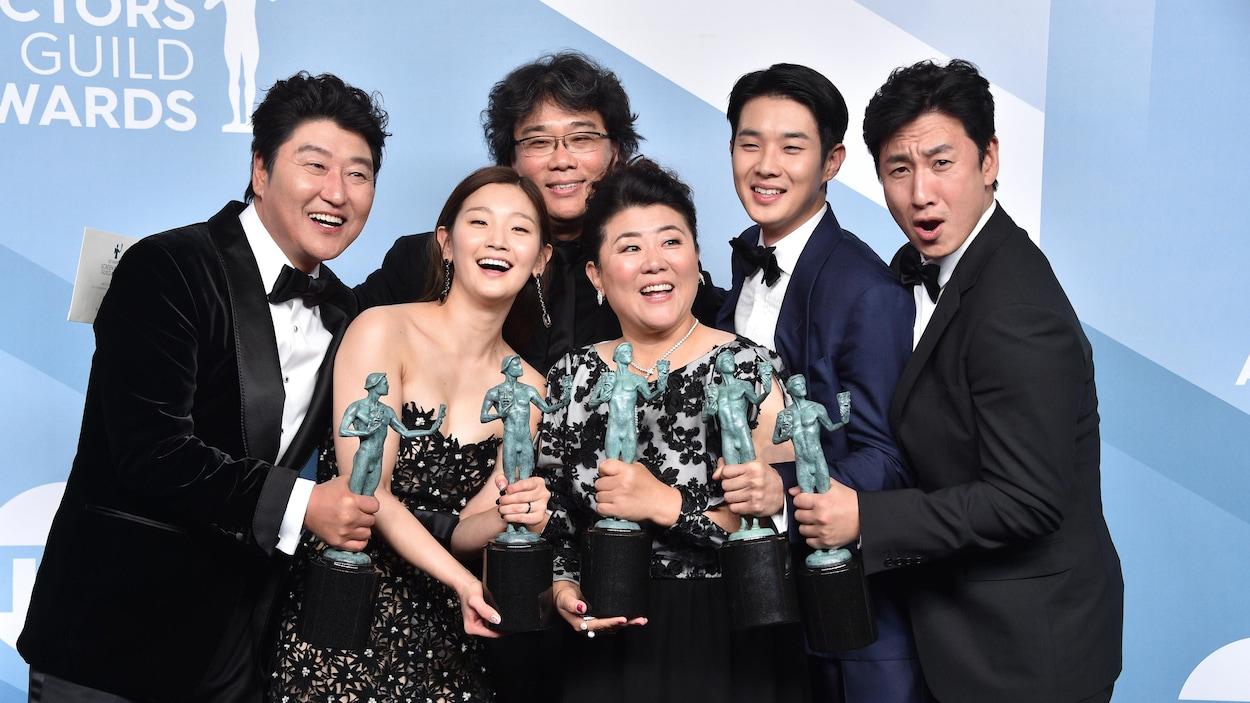 Six personnes tiennent des trophées dans leurs mains.