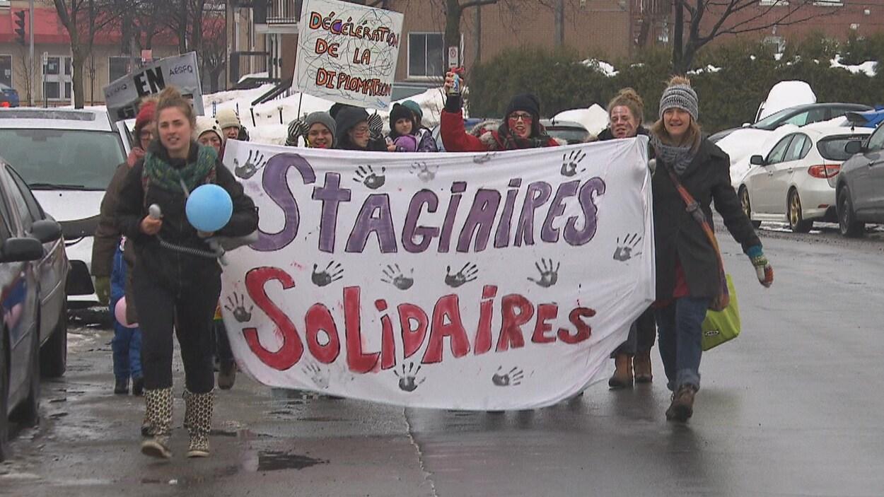 Des étudiantes tiennent une banderole où on peut lire « stagiaires solidaires ».